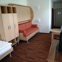 Schlafzimmer mit Kleiderschränken und TV im Gruppenhaus Simonyhof in Österreich.