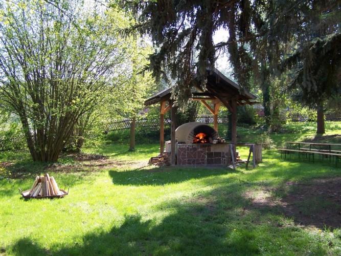 Feuerstelle mit Lehmbackofen im Garten am Freizeithaus Gästehaus Harz für barrierefreie Gruppenreisen in Deutschland.