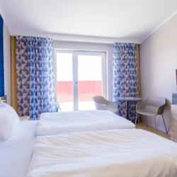 Ein Schlafzimmer im deutschen Gruppenhaus Kajüte auf Langeoog für barrierefreien Urlaub.