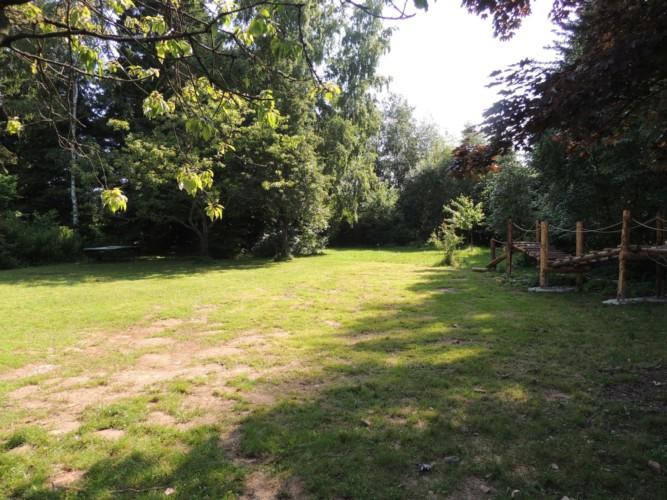 Garten mit Spielgeräten und großer Wiese am Freizeitheim Krekel in Deutschland.