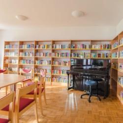 Gruppenraum mit Bibliothek, TV und Klavier im Gruppenhotel Zittauer Gebirge in Deutschland.