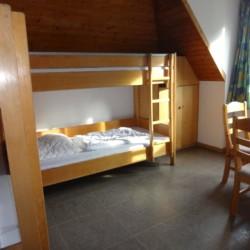 Ein Schlafzimmer mit Etagenbetten, Sitzgruppe und Kleiderschrank im Gruppenhaus Freizeitheim Settrup für Kinder und Jugendfreizeiten in Deutschland.