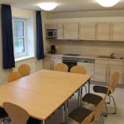 Ein Gruppenraum mit Küchenzeile, TV und Esstisch im dänischen Freizeithaus Tydal für Kinder und Jugendgruppen.