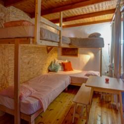 Ein Schlafzimmer mit Hochbetten und Sitzgruppe im Freizeithaus Strandlodges Olymp in Griechenland.
