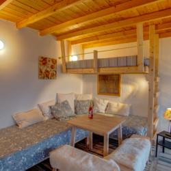 Ein Schlafzimmer mit Sitzgruppe und Hochbett im Freizeithaus Strandlodges Panorama in Griechenland.