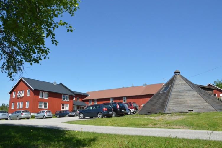 Das norwegische Sommerlager am See mit Lagerfeuerstelle.