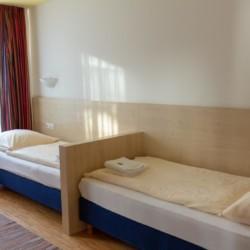 Ein Zimmer mit zwei Einzelbetten im Gruppenhaus Heringsdorf in Deutschland.