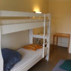 Dreibettzimmer im norwegischen Freizeitheim Haraset mit viel Wald und Natur drumherum.