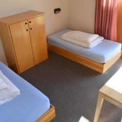 Ein Schlafzimmer mit Betten, Tisch und Kleiderschrank im irischen Freizeithaus Donegal Hostel.