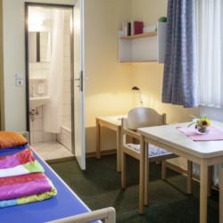 Ein Schlafzimmer mit eigenem Bad im Freizeithaus Heliand für Kinder und Jugendfreizeiten in Deutschland.