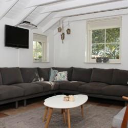 gemütliche Sitzecke mit TV im großen Gruppenraum mit Kaminofen im niederländischen rolligerechten Handicaphaus mit hohem Standard Het Keampke Haus Eik