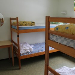 Holzbetten im Mehrbettzimmer im Freizeithaus Flahult Ungdomsgård in Schweden.