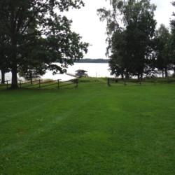Wiese und See am Freizeithaus Majblommegården in Schweden.