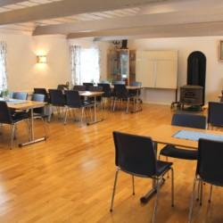 Speisesaal mit Kamin im Gruppenheim Tygegården in Schweden.