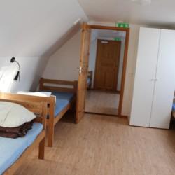 Holzbetten und Kleiderschrank in einem Mehrbettzimmer im schwedischen Gruppenhaus Tygegården für Kinder und Jugendreisen.