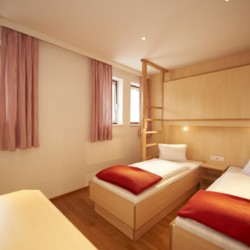 Ein Doppelzimmer im modernen barrierefreien Gruppenhaus Lindenhof in Österreich.