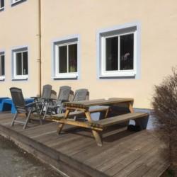 Die Terasse mit Sitzgruppe und Gartenstühlen am Gruppenhaus Haus Wendy in Österreich.