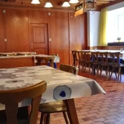 Der Speisesaal mit Sitzgruppen und Beamer im österreichischen Gruppenhaus Haus Wendy für Kinder und Jugendfreizeiten.