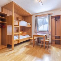 Ein Schlafzimmer mit Etagenbetten, Kleiderschränken und Sitzgruppe im Gruppenheim Haus Wendy in Österreich.