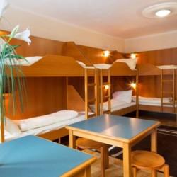 Ein Mehrbettzimmer mit Etagenbetten und Sitzgruppe im österreichischen Freizeithaus Haus Wendy für Gruppenreisen.