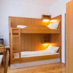 Ein Mehrbettzimmer mit Etagenbetten, TV und Kleiderschrank im österreichischen Freizeithaus Haus Wendy für Gruppenreisen.
