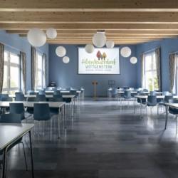 Ein Gruppenraum mit Leinwand, Beamer und Sitzgruppen im deutschen Freizeithaus Fuchsbau.