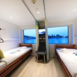 Eine Kabine mit Pflegebetten und großen Fenstern auf dem deutschen Flusskreuzfahrtschiff MS Viola für barrierefreie Gruppenreisen.