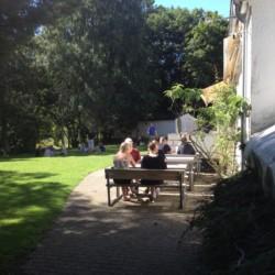 Außenbereich mit Wiese und Sitzbänken am Freizeithaus Hulemosegård in Dänemark.