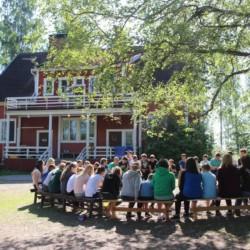 Sitzkreis unter Bäumen am finnischen Freizeithaus Vanamola für Kinder und Jugendgruppen.