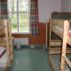 Ein Mehrbettzimmer mit Holzbetten im Gruppenheim Vanamola in Finnland am See.