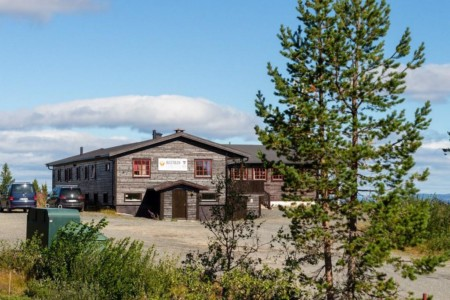 norwegisches Gruppenhaus im Hochfjell mit See und Gebirgspanorama