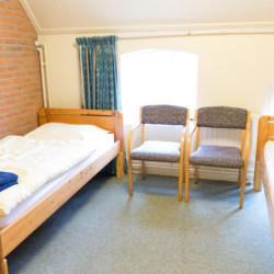Ein Schlafzimmer mit Einzelbetten im niederländischen Gruppenhaus De Boerschop.